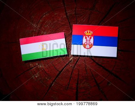 Tajikistan Flag With Serbian Flag On A Tree Stump Isolated