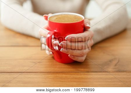 Woman holding a cup of hot drink while sitting at wooden table, shallow depth of field.
