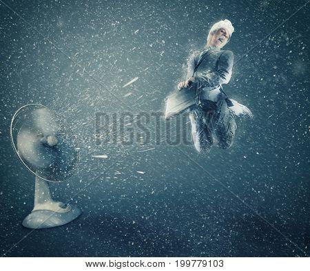 Businessman taking off the ground beside a powerful fan fan causing snow.