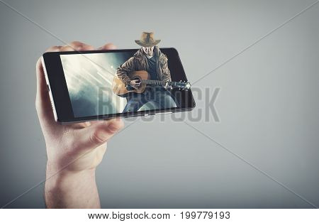 Hand holding a smartphone which displays live concert on touch screen.Cowboy playing guitar on stage and get out of the screen.