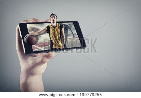 Hand holding a smartphone which displays a basketball match on the touch screen. Basketball player dribbling the ball out of the screen.
