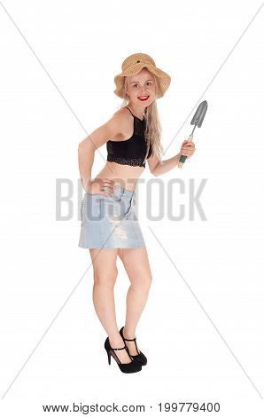 A beautiful blond woman with a straw hat and a small shovel ready for her work in the garden isolated for white background