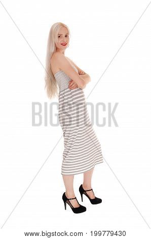 A gorgeous young woman in a long dress and hair standing in profile with her arms crossed isolated for white background