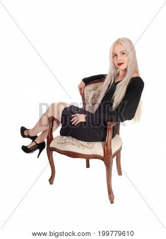 A lovely young woman with long blond hair sitting in an old armchair in a black dress isolated for white background