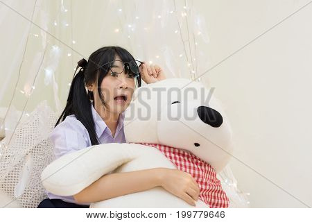 Cute Asian Thai high school girl in uniform and glasses show funny shocking facial expression while hugging fluffy teddy bear doll in soft cloth curtain decorate with feather and light in funny schoolgirl action concept.