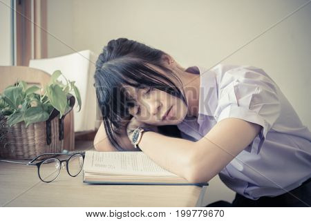 Shallow depth of field of cute Asian Thai high school girl in uniform fall asleep on the book on her dest during doing homework in fashion education concept in vintage color. Focus on arm and elbow and book.