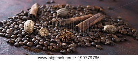 Close-up of roasted coffee beans and spices on dark background