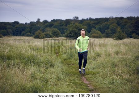 Fit muscular man jogging on a rural trail through grassland wearing sportswear in an active lifestyle concept