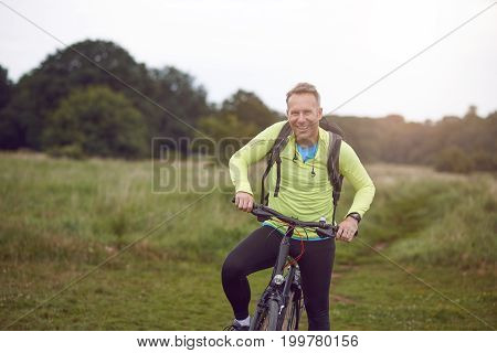 Smiling mature man wearing sportswear on bicycle tour through meadow