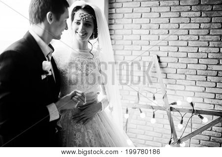Wedding Couple Posing Against Brick Wall With Star-shaped Light. Black And White Photo.