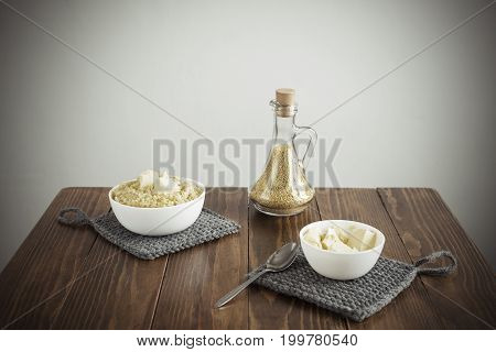 Millet porridge and butter on a wooden table. Manipulated soft image, vignette is added.