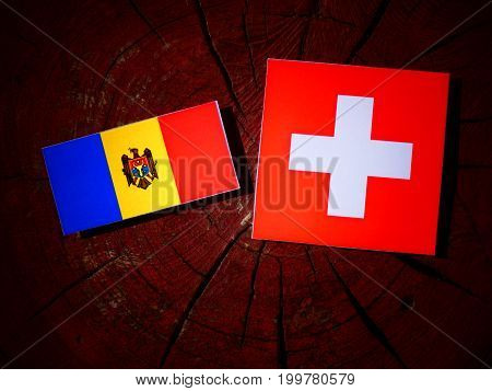 Moldovan Flag With Swiss Flag On A Tree Stump Isolated
