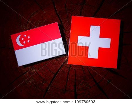 Singaporean Flag With Swiss Flag On A Tree Stump Isolated