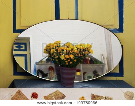 Creative space. Cozy home interior from an oval mirror, books, yellow flowers of carnations in a vase and a sofa with cushions against the background of a yellow door with blue stripes