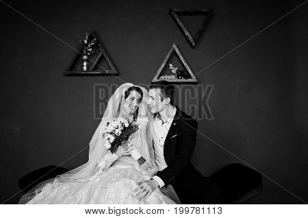 Fabulous Wedding Couple Sitting Against Blue Wall With Triangular Frames On It In The Studio. Black