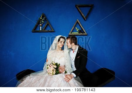 Fabulous Wedding Couple Sitting Against Blue Wall With Triangular Frames On It In The Studio.