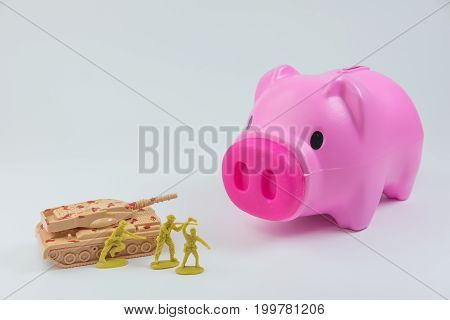 Pink piggy bank with tank and soldiers in concept of breaking bank for living.