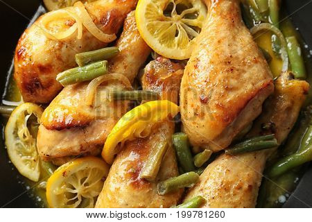 Delicious chicken drumsticks with sliced lemon in frying pan, closeup