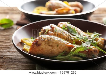 Plate with delicious roasted chicken drumsticks and sliced lemon on wooden table