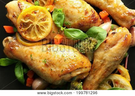 Delicious roasted chicken drumsticks with lemon on plate, closeup