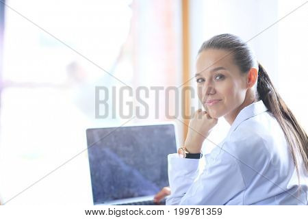 Beautiful young smiling female doctor sitting at the desk. Woman doctor