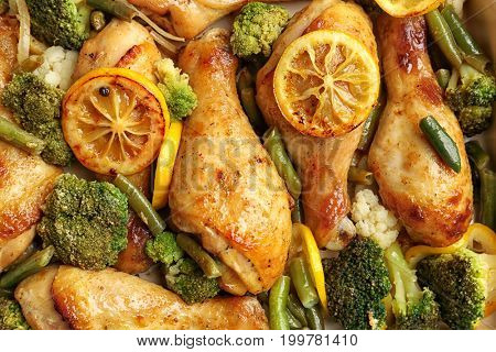 Delicious roasted chicken drumsticks with lemon and vegetables, closeup
