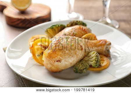 Plate with delicious roasted chicken drumsticks and lemon on table