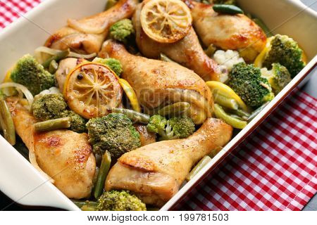 Baking dish with delicious roasted chicken drumsticks, lemon and vegetables on tablecloth