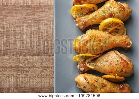 Plate with delicious roasted chicken drumsticks and lemon on wooden table