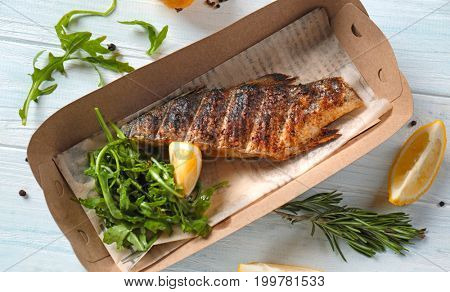 Cardboard box with delicious fish and arugula on table