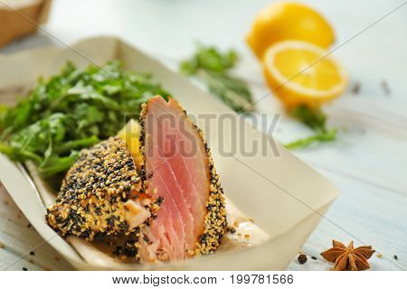 Delicious cooked fish with lemon and arugula, closeup