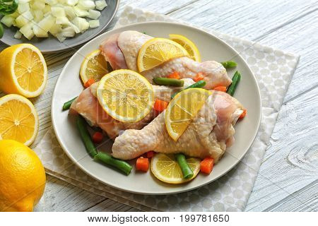 Plate with raw chicken drumsticks and lemon on light wooden table