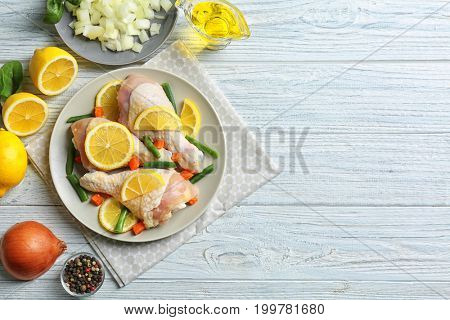 Raw chicken drumsticks with lemon and ingredients on light wooden table