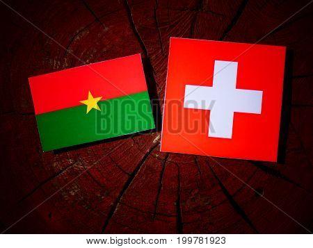 Burkina Faso Flag With Swiss Flag On A Tree Stump Isolated