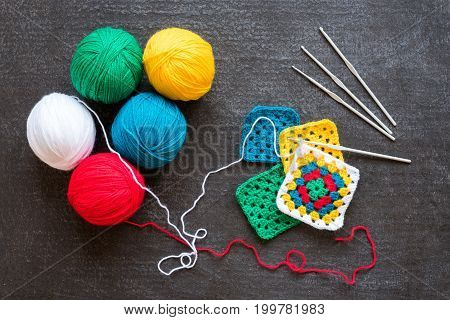 Balls of red and white yarn and crocheted motifs on grunge black background.