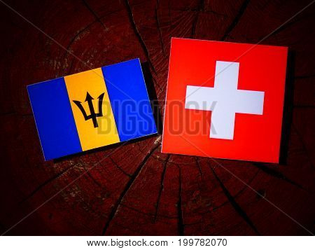 Barbados Flag With Swiss Flag On A Tree Stump Isolated