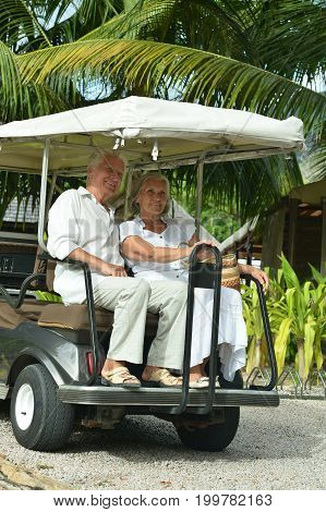 Happy elderly couple moving on cart on territory of hotel