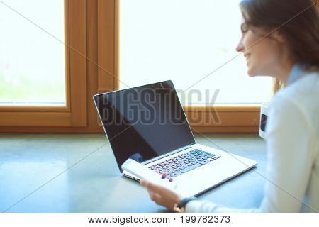 Young female standing near desk. Woman in the kitchen. Workplace