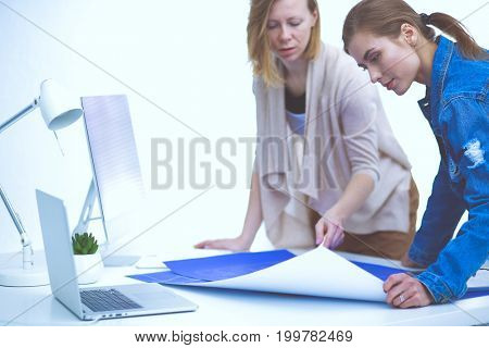 Two young woman standing near desk with instruments, plan and laptop.
