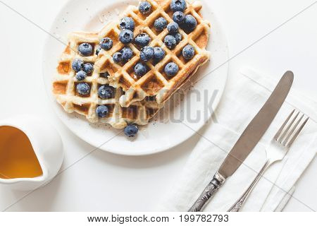 Top View Of Plate Of Tasty Fresh Waffles With Blueberries, Honey And Cutlery