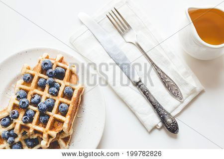 Top View Of Plate Of Delicious Waffles With Blueberries, Honey And Cutlery