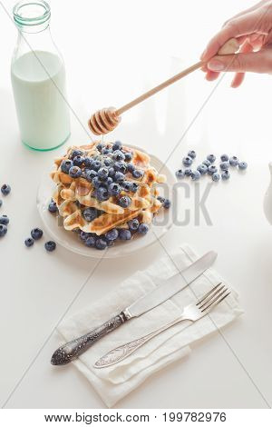 Cropped Shot Of Woman Pouring Honey On Tasty Stacked Waffles