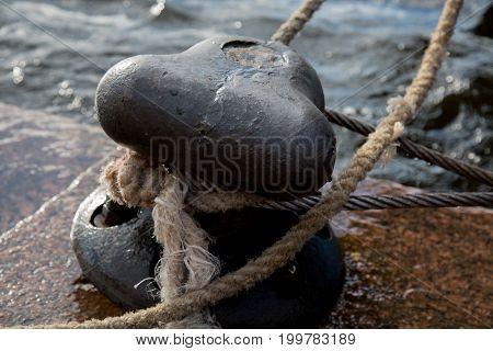 Close up metal mooring bollard background anchor marina knot