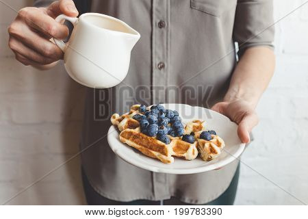 Cropped Shot Of Woman Pouring Syrup On Tasty Waffles