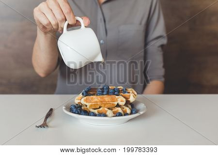Cropped Shot Of Woman Pouring Sweet Syrup On Tasty Waffles