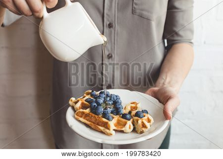 Cropped Shot Of Woman Pouring Maple Syrup On Tasty Waffles