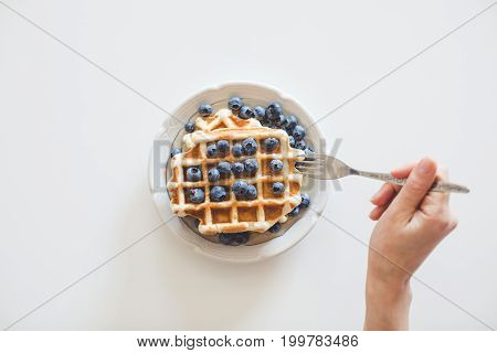 Top View Of Woman Eating Waffles With Blueberries For Breakfast