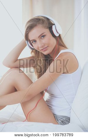 Portrait of beautiful woman in morning listening music sitting on bed at home. Portrait of beautiful woman