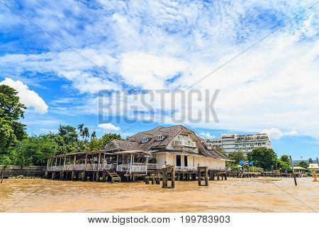 Beautiful white house by the Chao Phraya River against a clouds and blue sky.