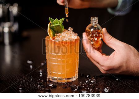 small skull-shaped bottle orange mohito cocktail and barmen hand
